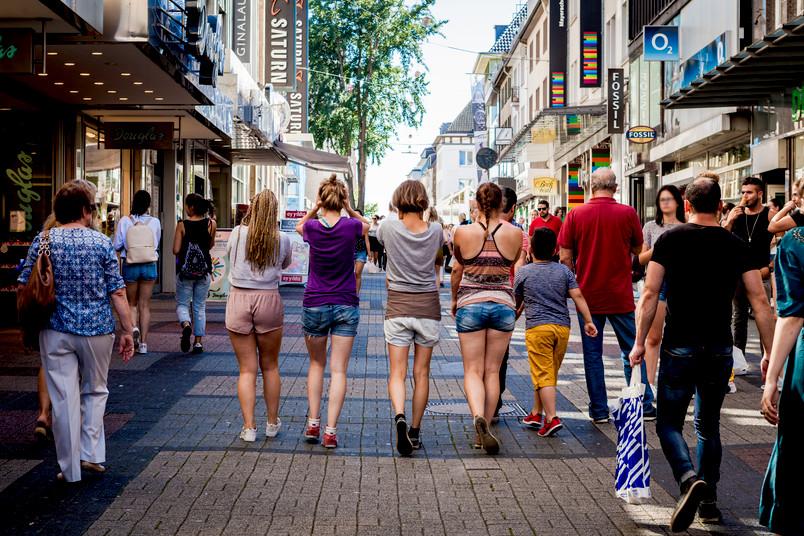 Rückenansicht von vier Studentinnen, die in der Fußgängerzone nebeneinander hergehen.