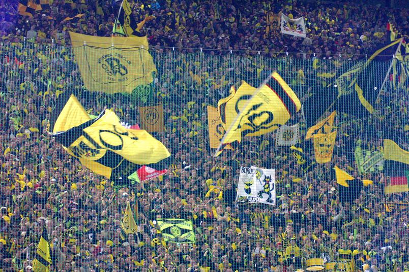 Fußball-Fans von Borussia-Dortmund schwenken Fahnen.