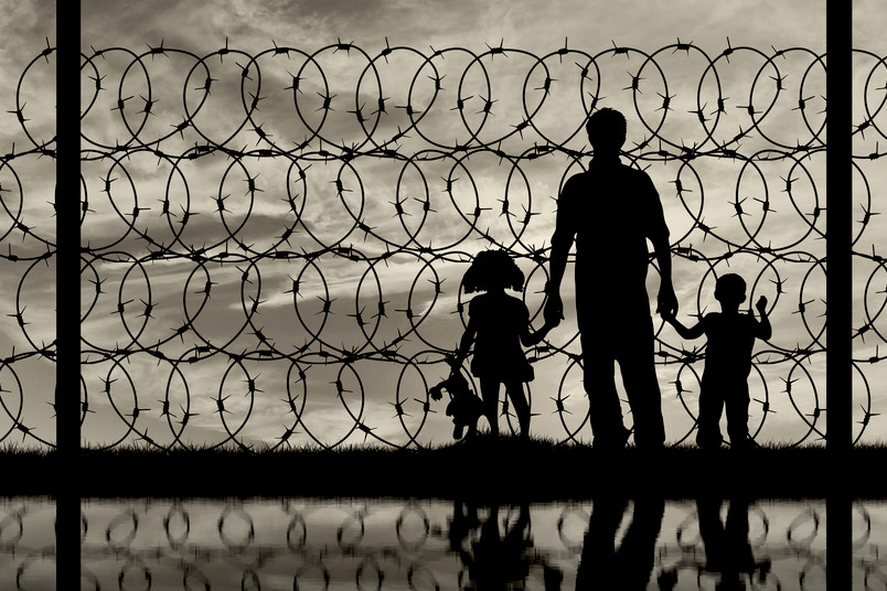 Silhouette Familie vor Stacheldraht