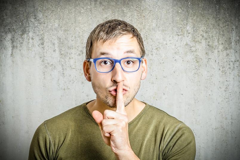 Ein mann hält sich den Zeigefinger vor den Mund.