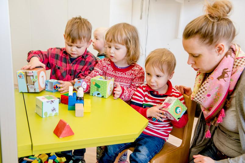 Drei Kleinkinder spielen zusammen mit einer Erzieherin.