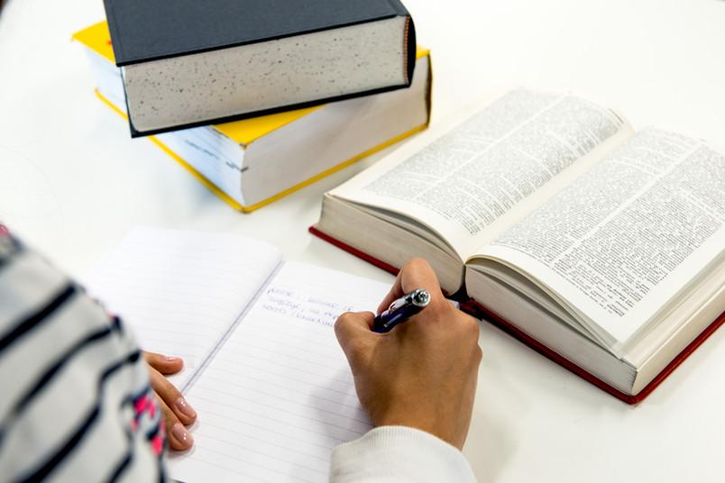 Studentin schreibt einen Text ab. Vor ihr liegen Bücher.