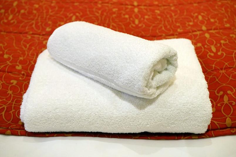 zwei weiße, auf einem Bett liegende Handtücher