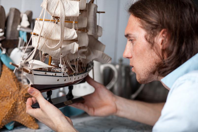 Junger Mann schaut Segelschiff an