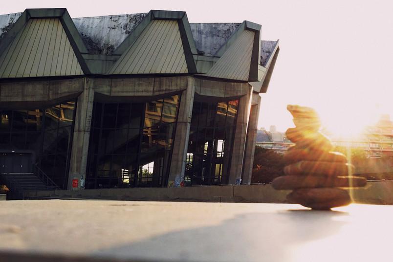 Audimax bei Sonnenaufgang mit Steinmannli im Vordergrund