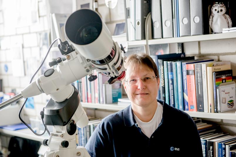 Eine Frau blickt in ihrem Büro durch ein Teleskop
