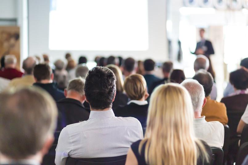 In einem Konferenzraum hören Tagungsteilnehmer einem Referenten zu.