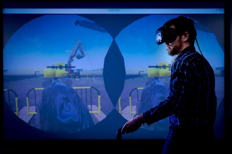 Ein Mann mit Virtual-Reality-Brille bewegt sich vor einer Projektionsfläche.