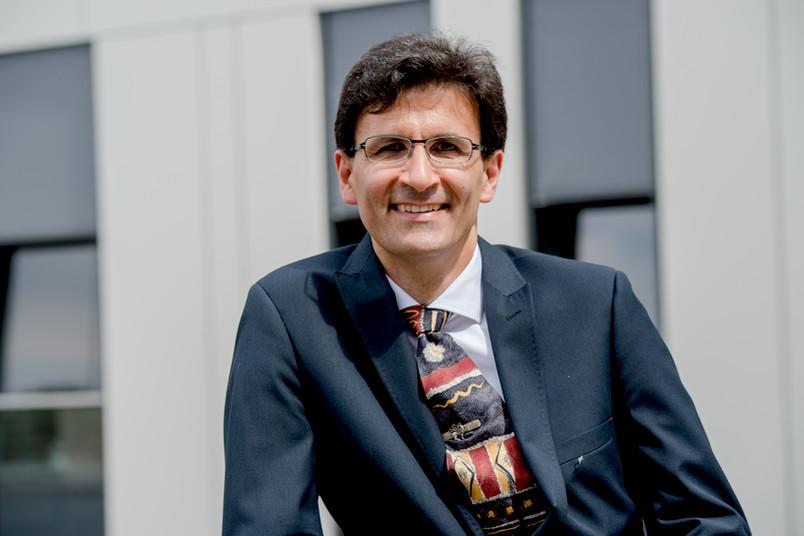 Mann mit Brille im Anzug, im Hintergrund das Unigebäude FNO