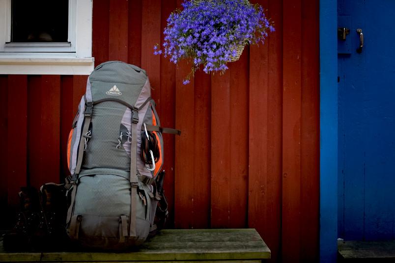 Ein Wanderrucksack steht auf einer Bank vor einem skandinavischen Haus.
