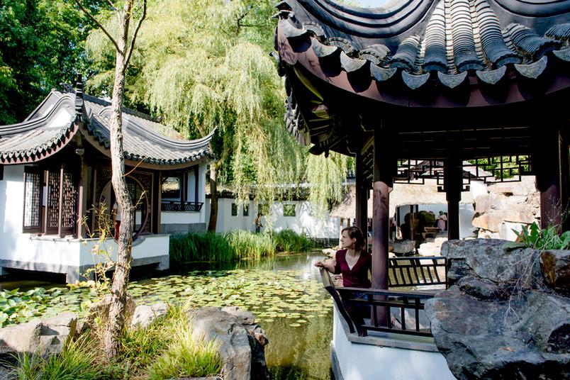 Junge Frau sitzt in einem Pavillon vom Chinesischen Garten.