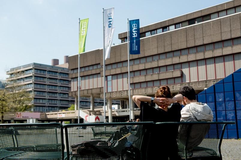 Studenten sitzen auf einer Bank vor der Kunstsammlung.