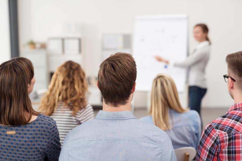 Eine Gruppe junger Leute hört einer Vortragenden zu.