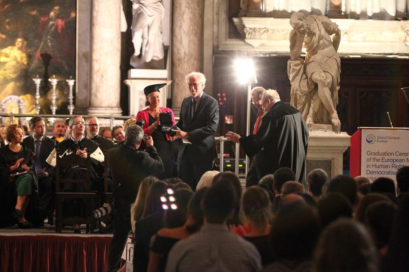 Viele festlich gekleidete Personen in einem kunstvoll gestalteten Raum in Venedig