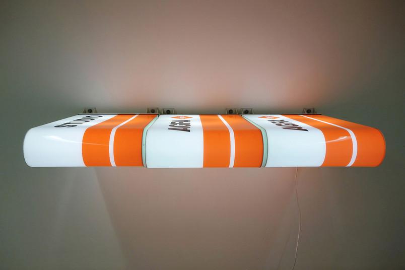 weiß-orangenes Kunstwerk hängt an der Wand