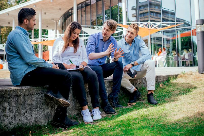 Vier Studierende unterhalten sich angeregt auf dem Campus.