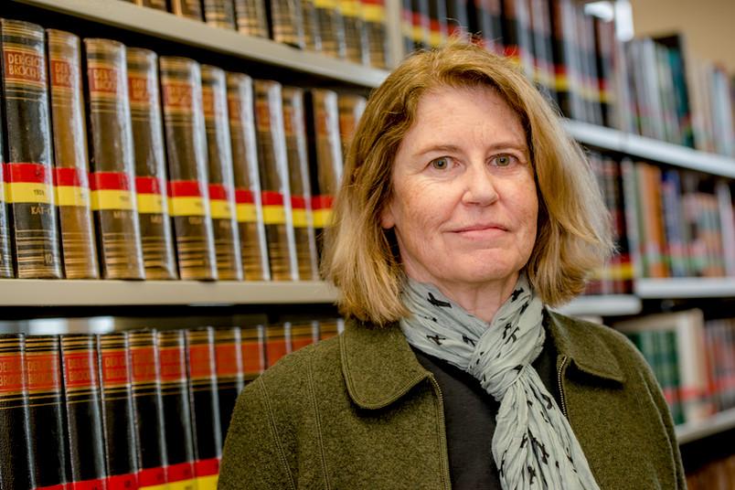 Porträt einer Frau, im Hintergrund Bücherregale