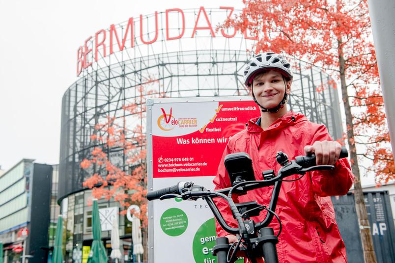 Student mit Fahrradhelm präsentiert sein Lastenfahrrad.