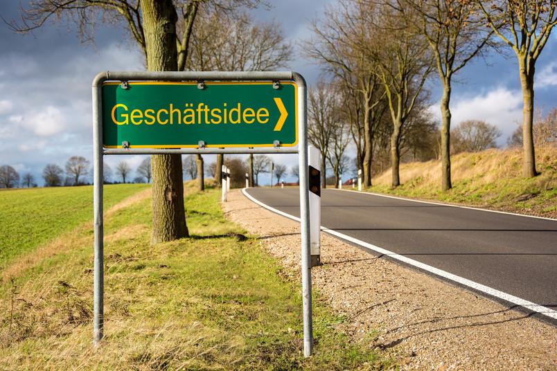 Ortseingangschild an einer Landstraße auf dem Geschäftsidee steht.