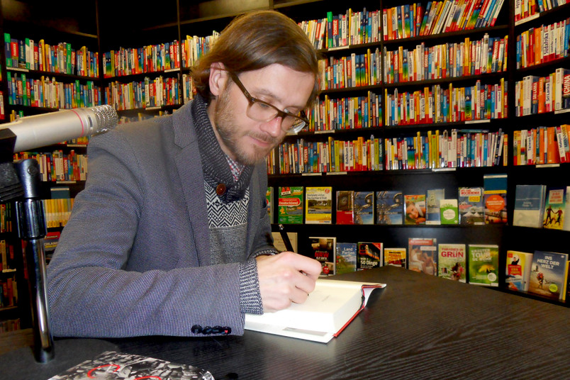 Junger Mann am Schreibtisch signiert ein Buch