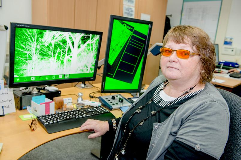Frau sitzt an einem Schreibtisch mit einem grünen Computerbildschirm.