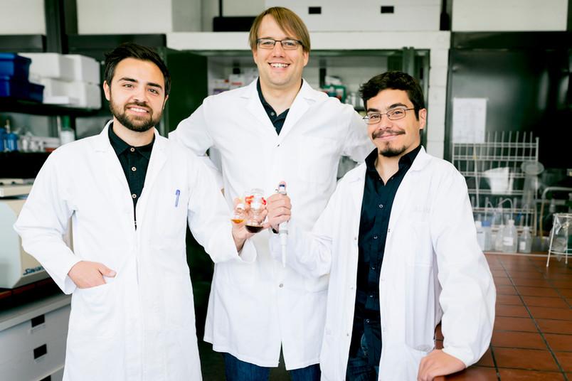 Drei Männer im Kittel stehen im Labor und halten Gefäße mit Flüssigkeiten in der Hand.