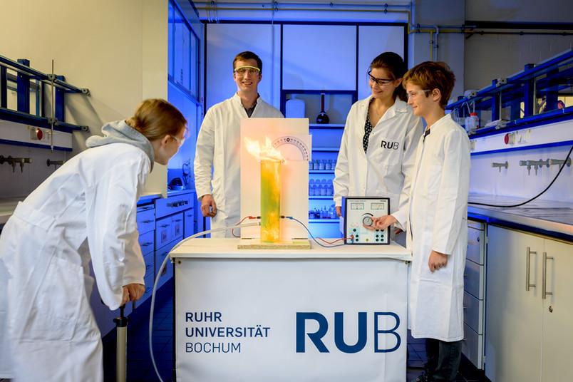 Zwei Kinder und zwei Forscher beobachten, wie eine Flamme aus einem Plexiglaszylinder schießt.