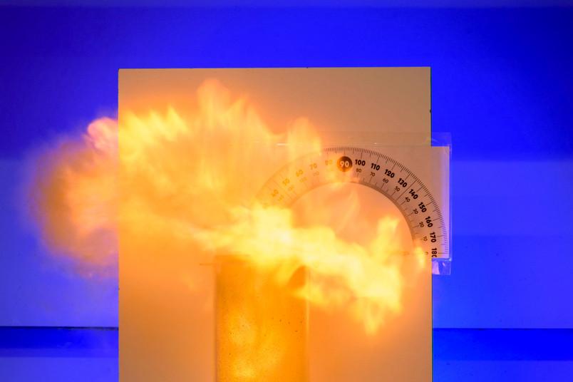 Feuer quillt aus einem Plexiglaszylinder.