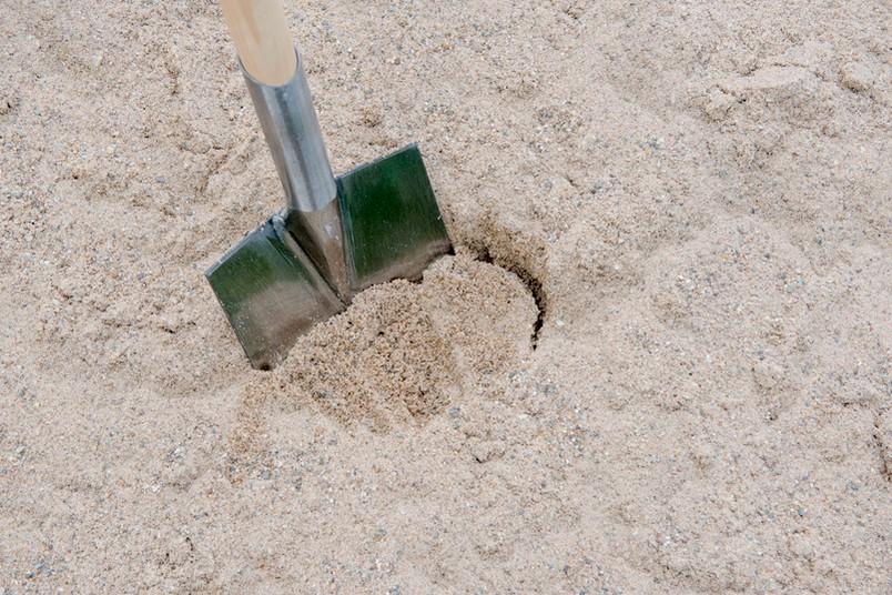 Spaten im Sand: ein Stellvertreterbild für den Spatenstich