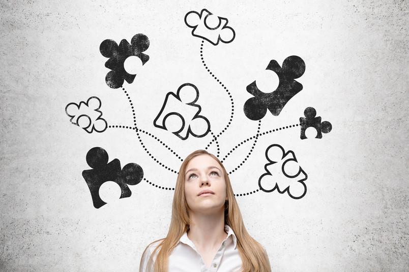 Frau umgeben von Puzzleteilen