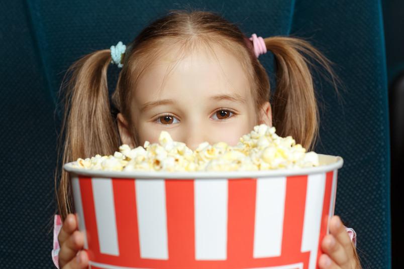 Mädchen schaut hinter einer Tüte Popcorn hervor.