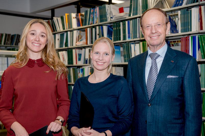 Zwei junge Wissenschaftlerinnen und ein Mann vor einem Bücherregal.