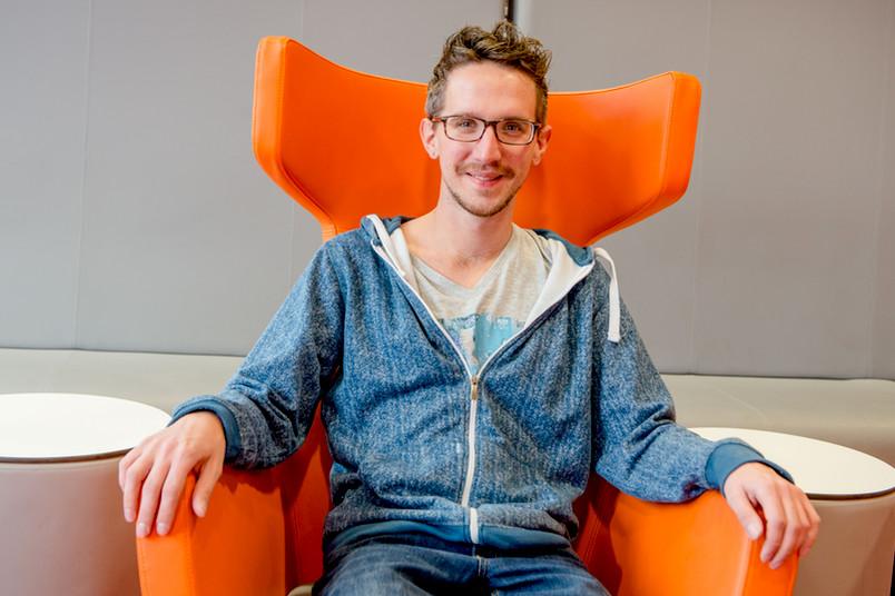 Der Student Julian Brock sitzt in einem orangenen Sessel.