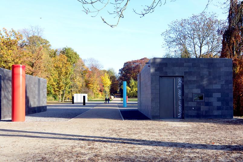 Eingang zu einem in einem herbstlichen Park gelegenen, unterirdischen Museum