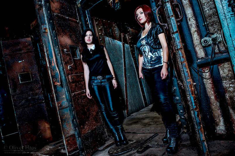 Zwei junge Frauen in dunkler Kleidung stehen vor einem Industriegebäude