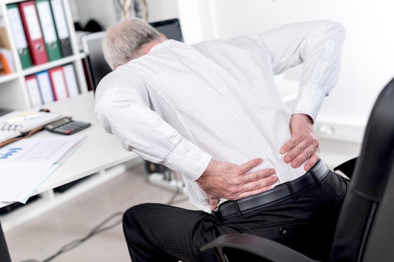 Mann krümmt sich am Schreibtisch vor Schmerz