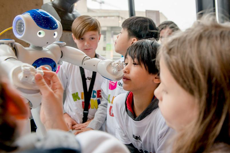 Kinder umringen einen kleinen Roboter.