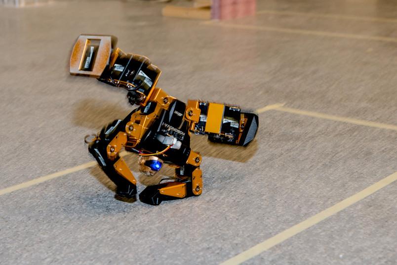 Ein kleiner gelber Roboter macht einen Radschlag.