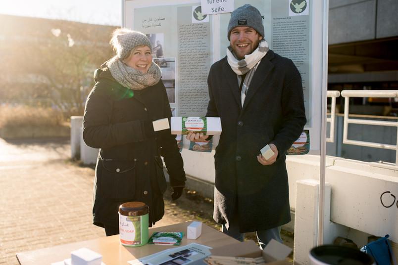 Studentin und Student stehen in der winterlichen Sonne und verkaufen Seifen.