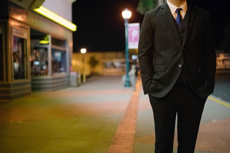 Mann in schwarzem Anzug steht auf Straße