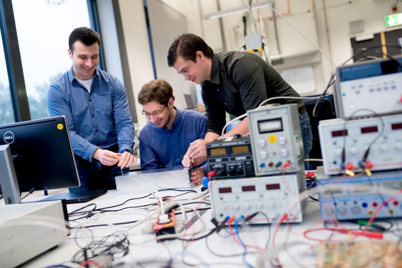 Drei Forscher zwischen Messgeräten