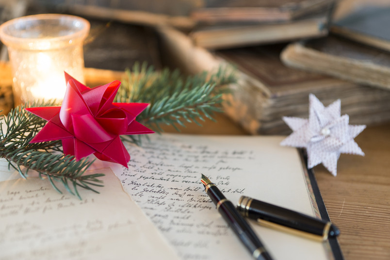 Füller und handgeschriebene Seiten inmitten von Weihnachtsdekoration.
