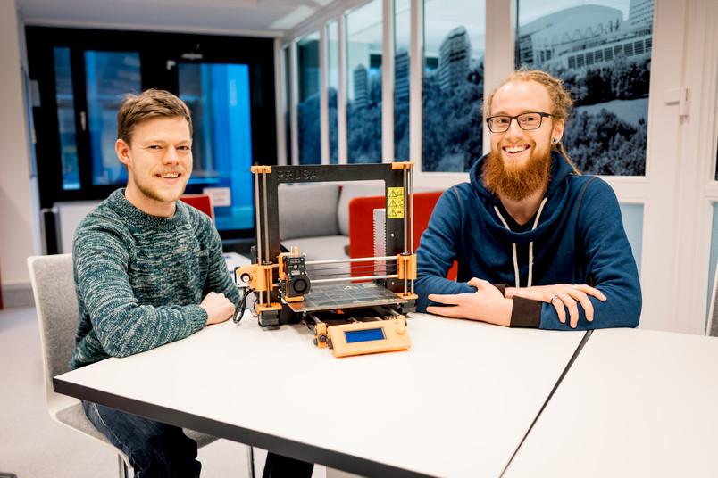 Zwei Studierende mit einem 3D-Drucker.