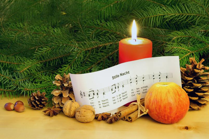 Kerze vor Tannenzweigen und einem Liedtext