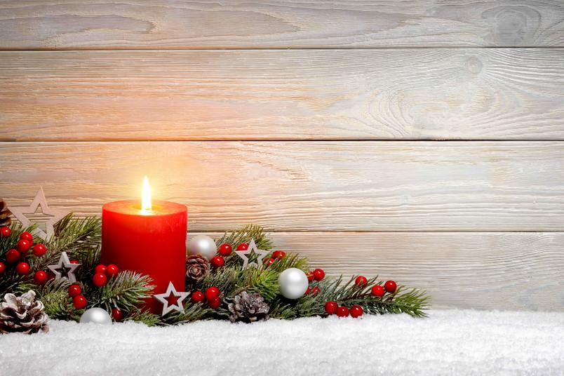 Weihnachtsmotiv mit roter Kerze und Tannenzweigen