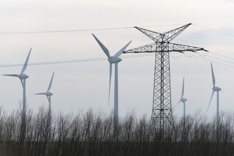 Windkrafträder und Strommasten in Ostfriesland.