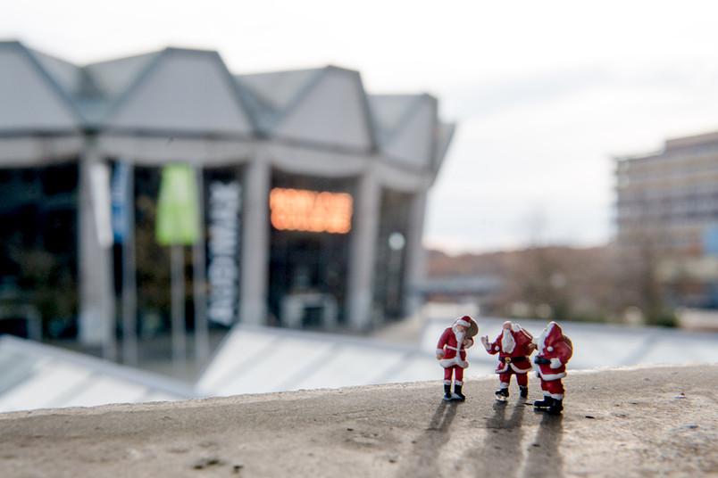 Drei kleine Weihnachtsmannfiguren und das Audimax im Hintergrund