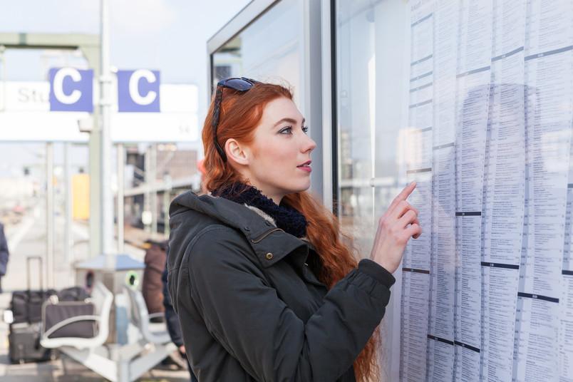 Junge Frau schaut am Bahnhof auf einen Fahrplan.