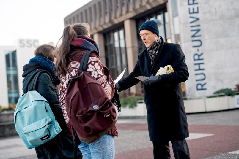Mann verteilt Flyer an zwei Studentinnen.