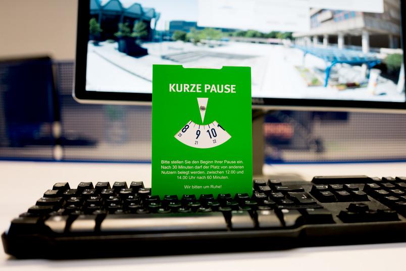 """Eine grüne Parkscheibe, auf der """"Kurze Pause"""" steht, steckt in einer Tastatur vor einem PC-Bildschirm."""